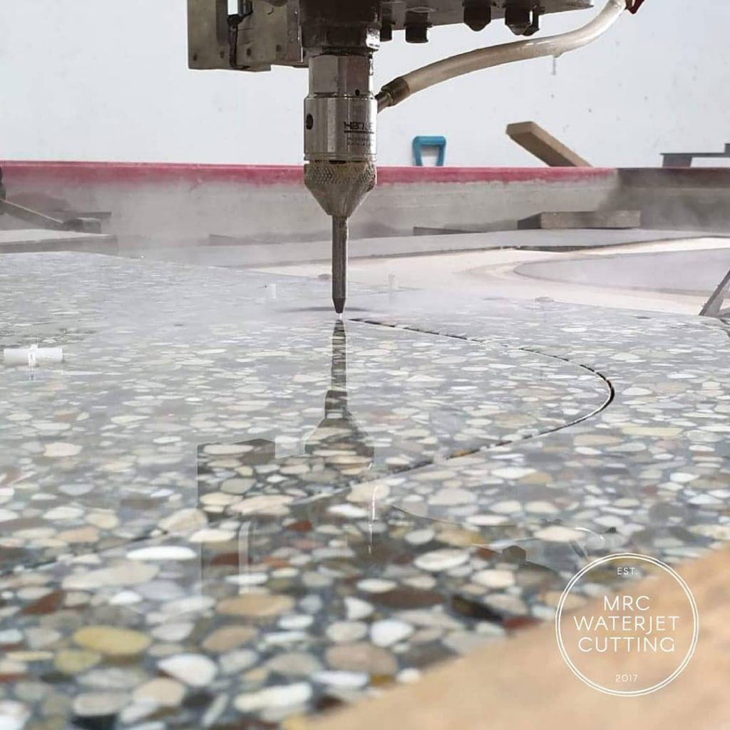 Waterjet cutting terrazzo tiles for an underhung bath. Doing it like this gives the tiler a perfect shape to frame the bath.